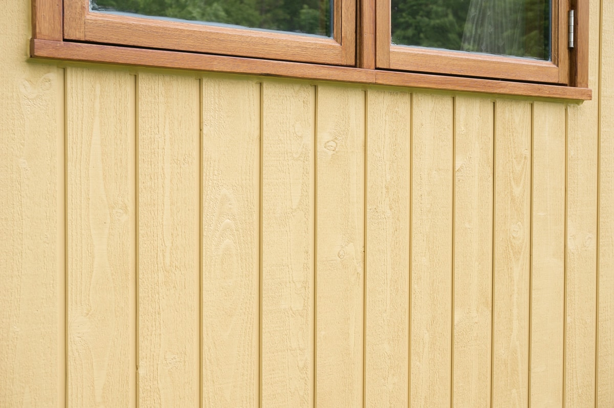 yellow painted solid wood siding on a shepherd hut exterior