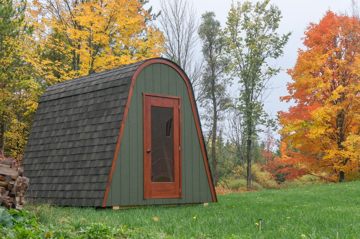 a green Haliburton Gute cabin in an Ontario backyard