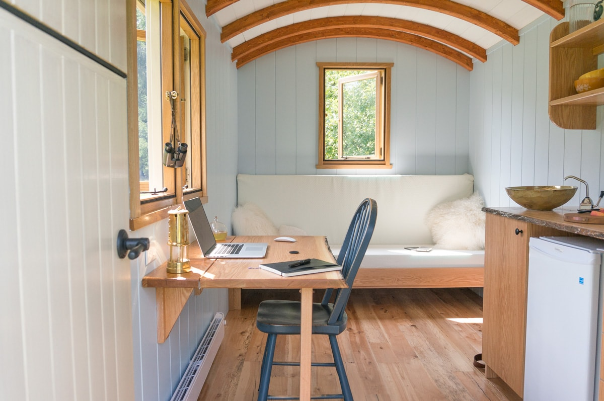 a shepherd hut door opening into its furnished interior