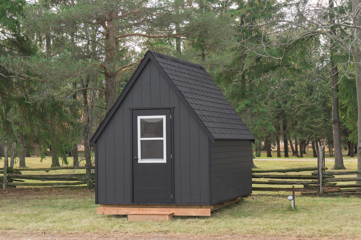 a black Killarney Gute cabin hut in an ontario backyard