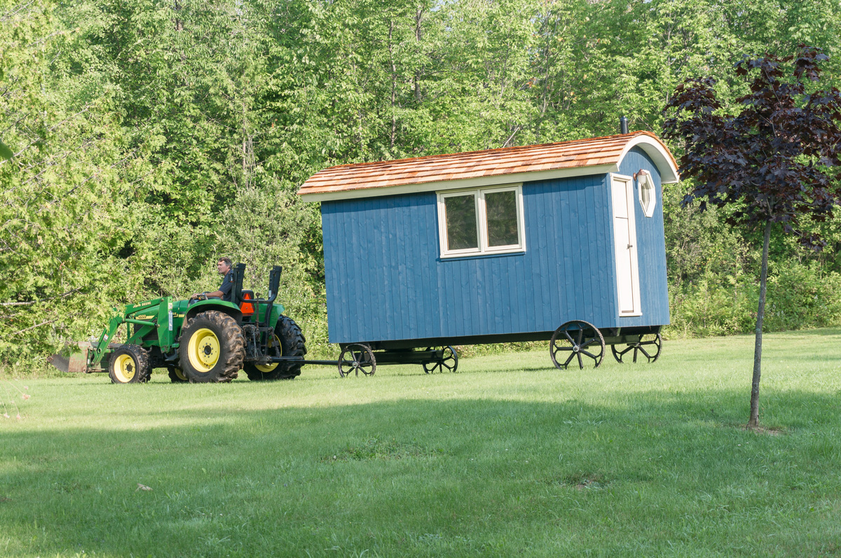 a gute shepherd hut being moved by a tractor in a grass field