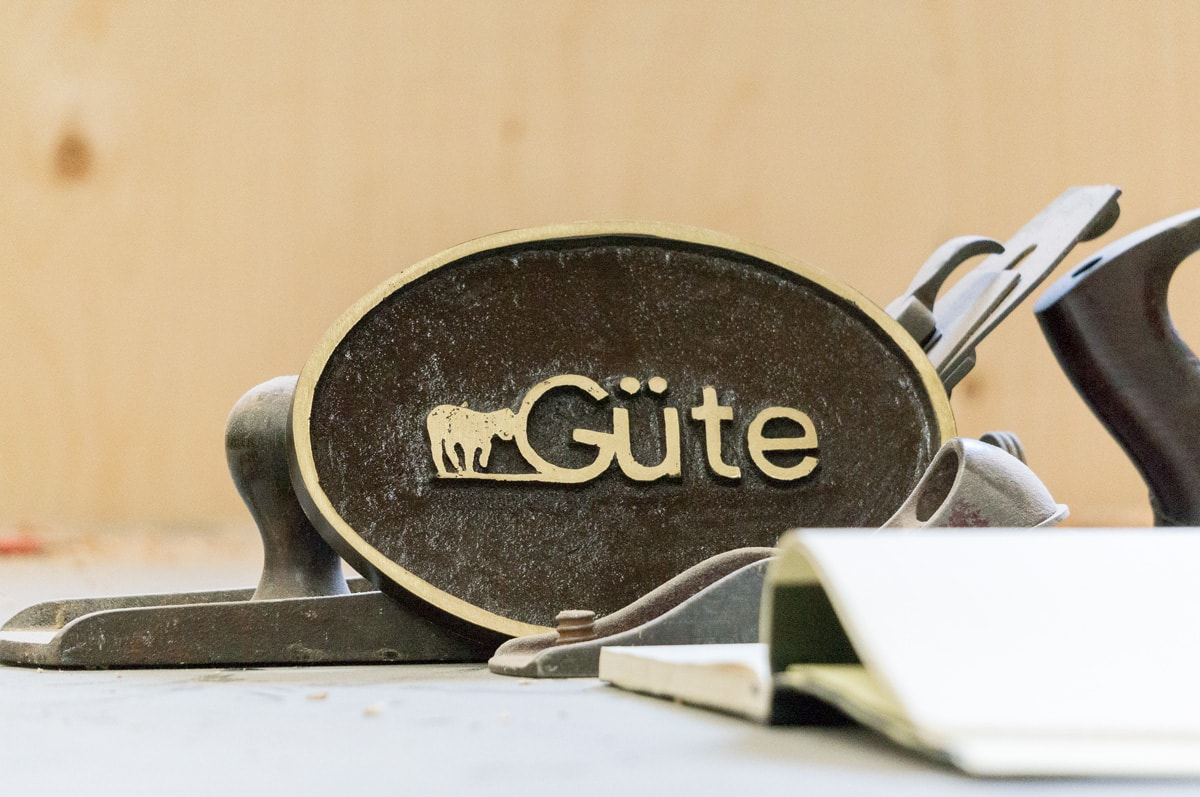 a gute logo plaque resting against a handplane on the workbench