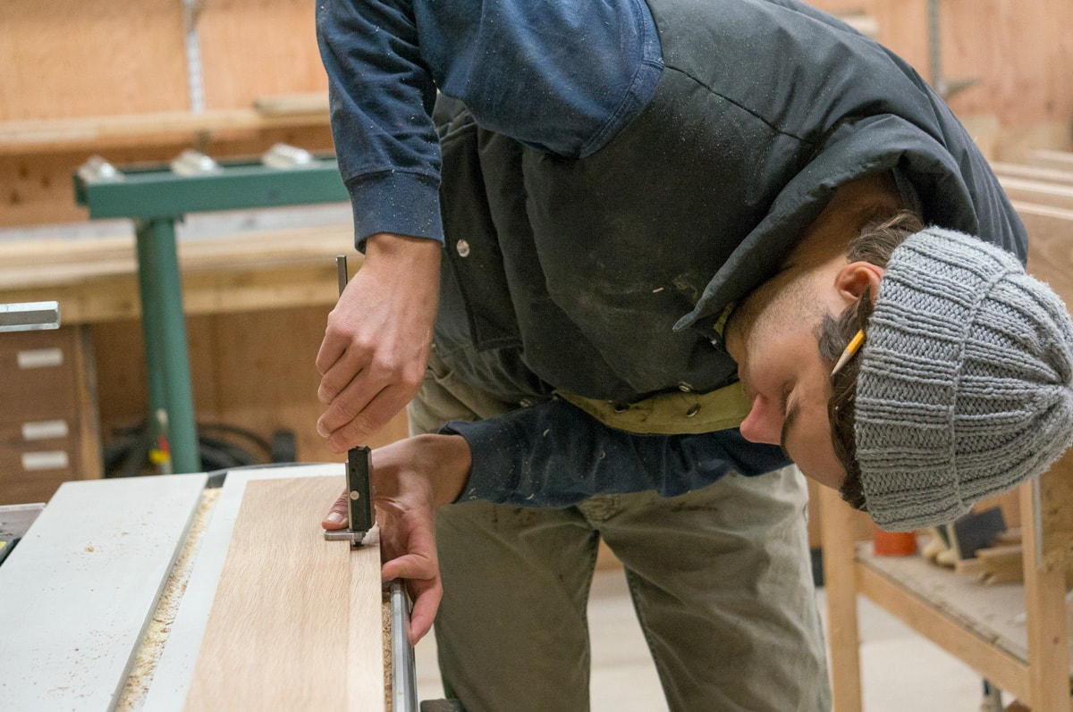 evan using a caliper to measure an oak board's thickness