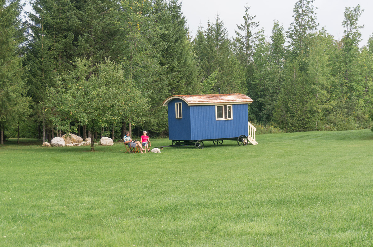 a blue classic shepherd hut in a backyard with a couple sitting next to it