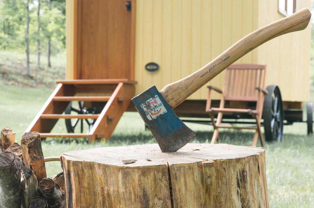 an axe in a log in front of the entrance to a shepherd hut