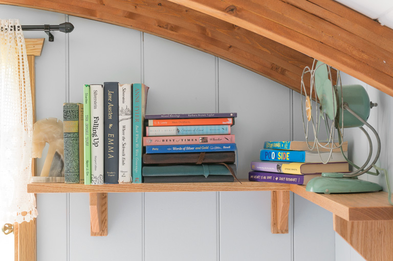 a gute oak shelf with books and a fan
