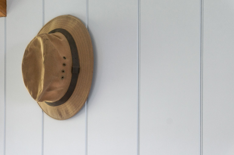 a tilly hat hanging on the shepherd hut wall