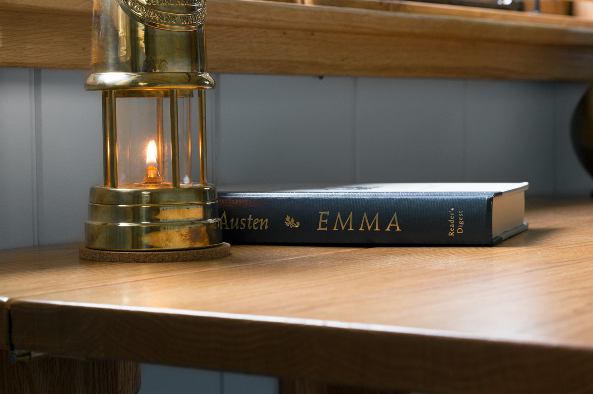 a lit welsh miner's lamp sitting beside a Jane Austen Novel