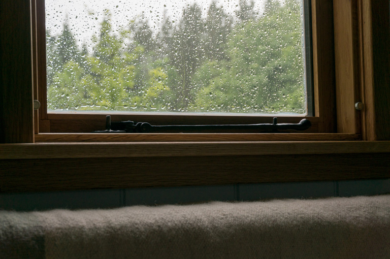 a gute oak window from the inside with rain drops