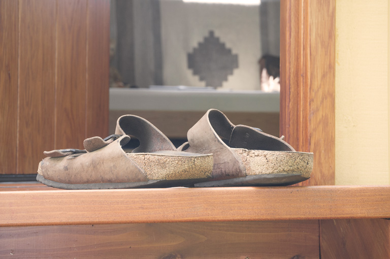 a pair of birkenstocks in front of an open shepherd hut door